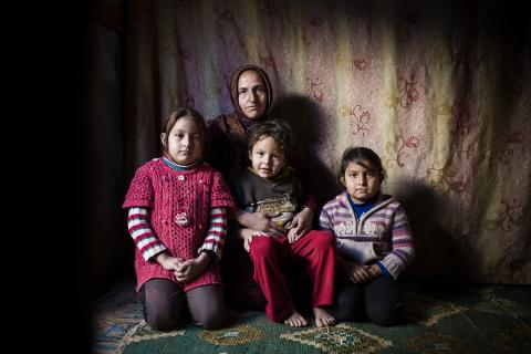 A woman sits with three children, Lebanon