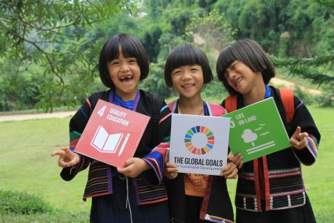 Three young girls smile outside in Thailand while posing with posters for the SDGs.