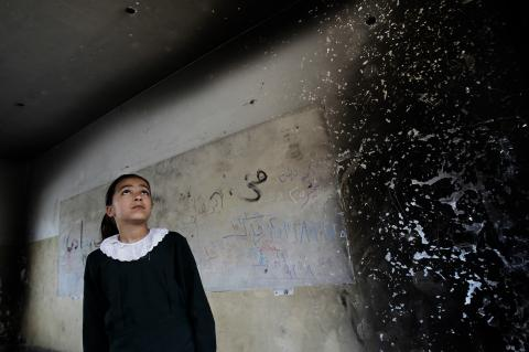 A girl looks inside one of the classrooms that were destroyed during the 2014 hostilities.
