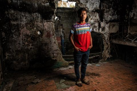 Philippines. A boy stands in the remains of a building.
