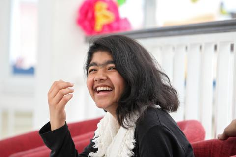 An Afghan teenage girl laughing