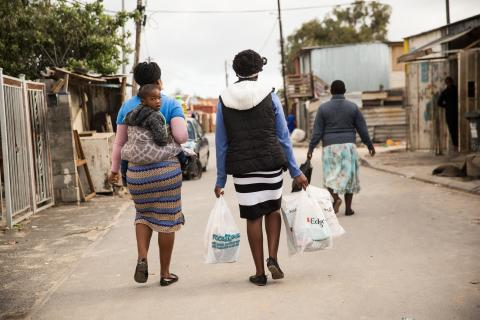 Child obesity South Africa: Women and children walking down a street in Cape Town