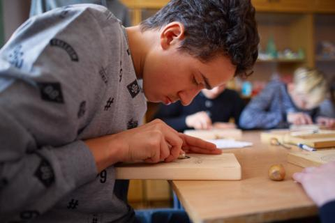 Volodymyr Charushyn, 16, at the wood carving lesson at his education complex for children with hearing disabilities in Ukraine He is a grantee of UPSHIFT Ukraine, an innovative programme aimed at developing entrepreneurship skills among adolescents and youth as agents of social change.
