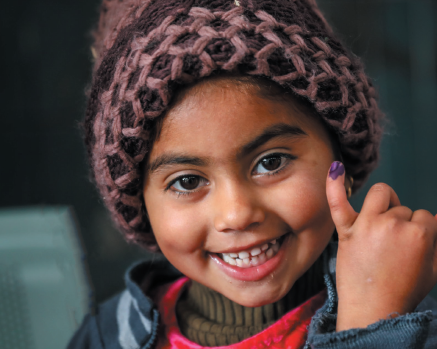 A girl happily shows the ink mark of her little finger; sign of being vaccinated.