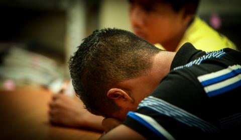 A boy puts his head down on a desk, El Salvador