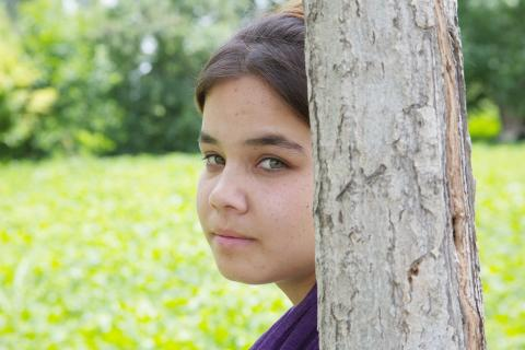 A girl leans against a tree, Uzbekistan
