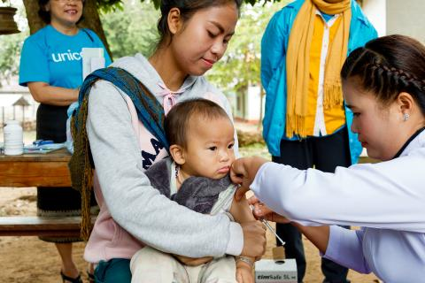 A woman holds a baby who is vaccinated, Laos