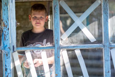 Ukraine. A boy looks out of the window of his home.