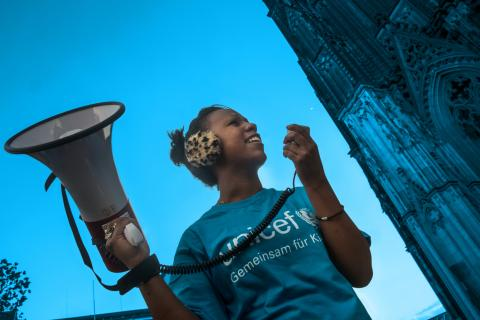 A girl in a blue UNICEF tee and holding a megaphone