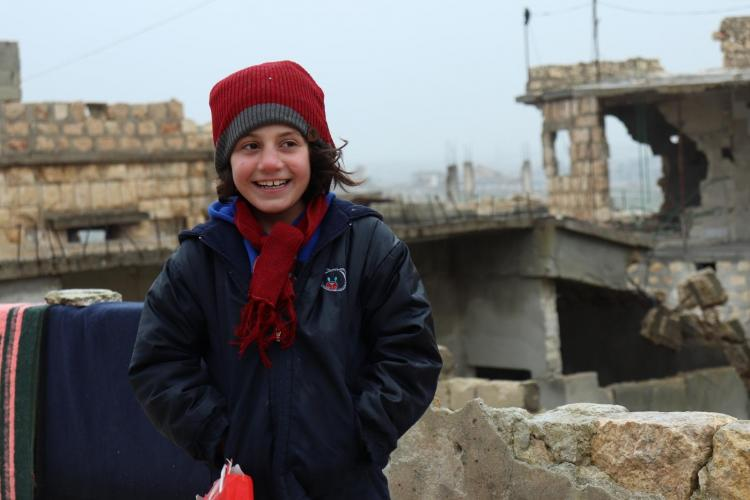 A Syrian girl wearing a warm hat she received as part of a youth-led initiative