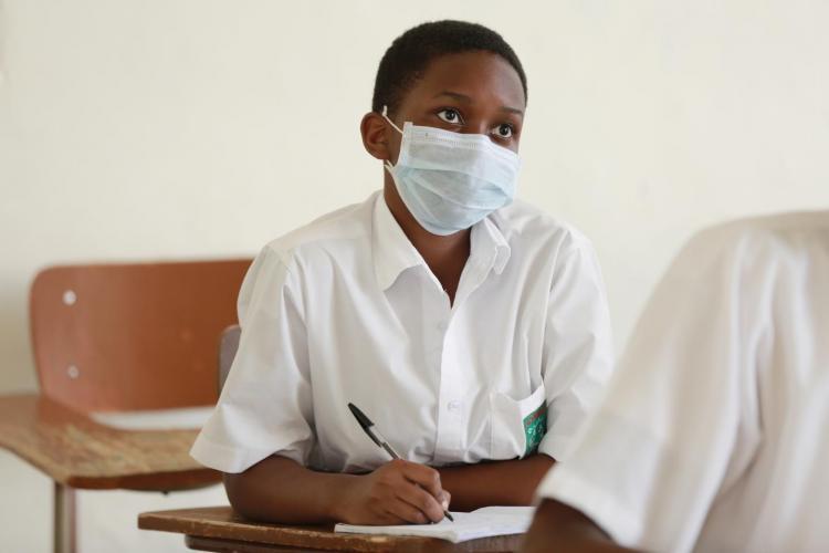 Rwanda. A teenager sits at a desk in a classroom.