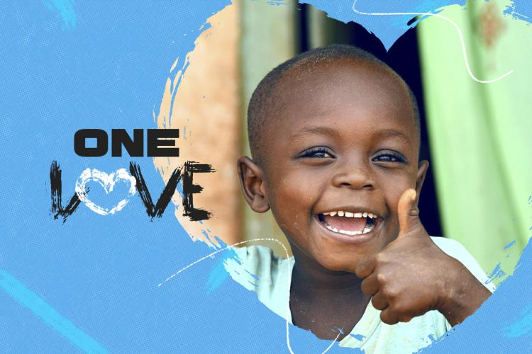"Photo of a child giving a thumbs up with the text reading ""One Love"""