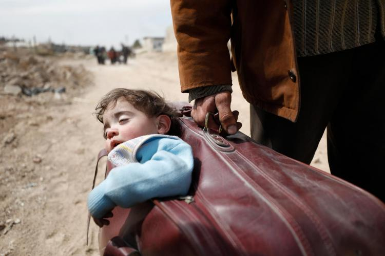 A man carries a child in a suitcase in eastern Ghouta, Syria.