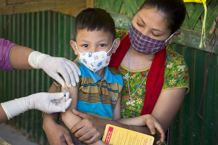 Bangladesh. A boy sits on his mother's lap as he receives a vaccination.