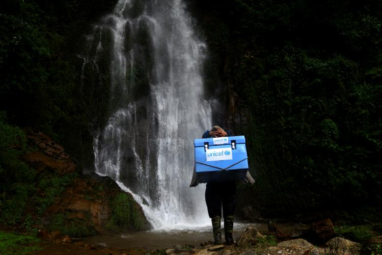 A porter carries UNICEF-provided vaccines on difficult terrains on the way to a measles, rubella and polio vaccination campaign to be conducted at Barpak Village Development Committee (VDC) health post in Gorkha District, the epicentre of the April 25 earthquake.