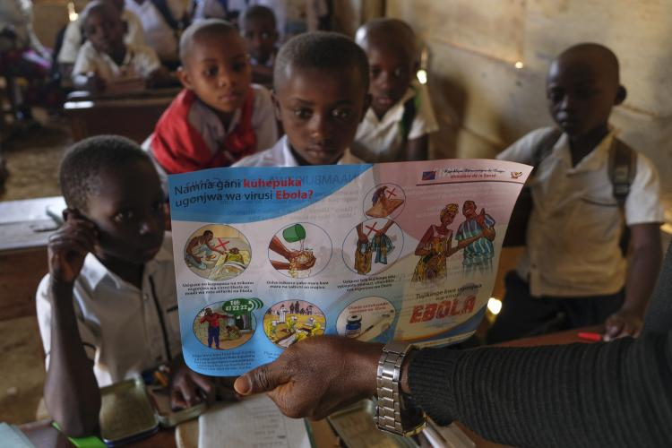DRC. Children look at a leaflet about Ebola