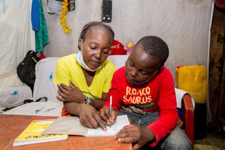 On 7 May 2020, Brian (right), 10, does schoolwork with the help of his mother, Gladys, at home in the Mathare informal settlement in Nairobi, Kenya.