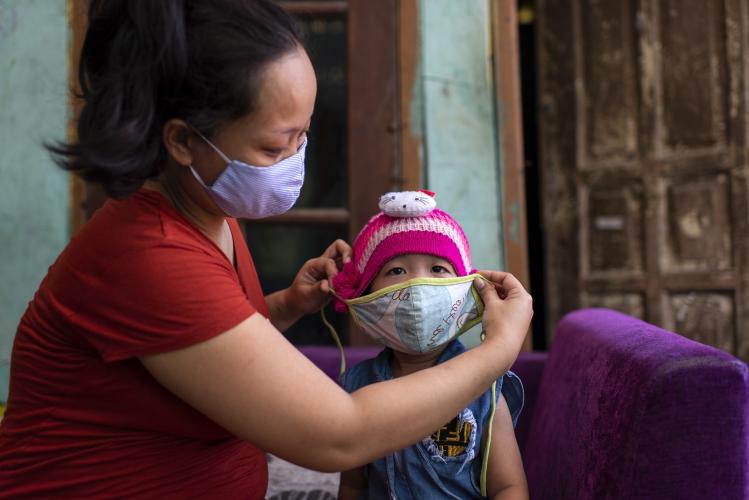 Indonesia. A woman puts a face mask on a child.