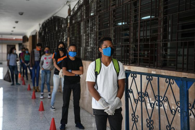 Venezuela. Students wearing facemasks line up outside their school.