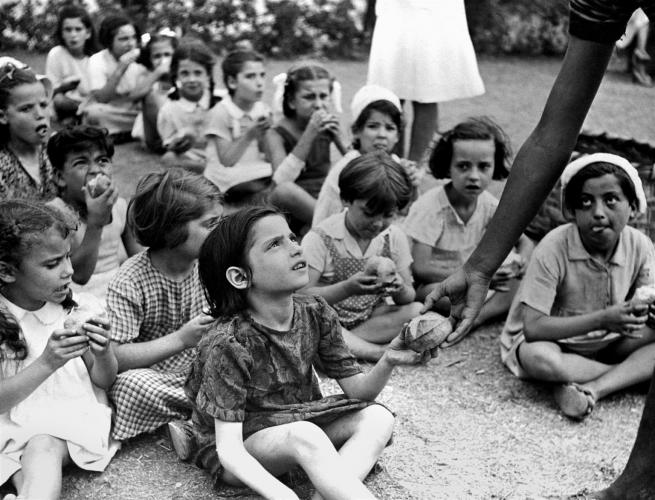 Children seated on the ground accepting food