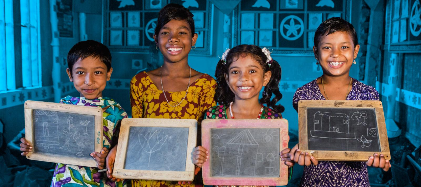 Four girls hold drawings on chalkboards