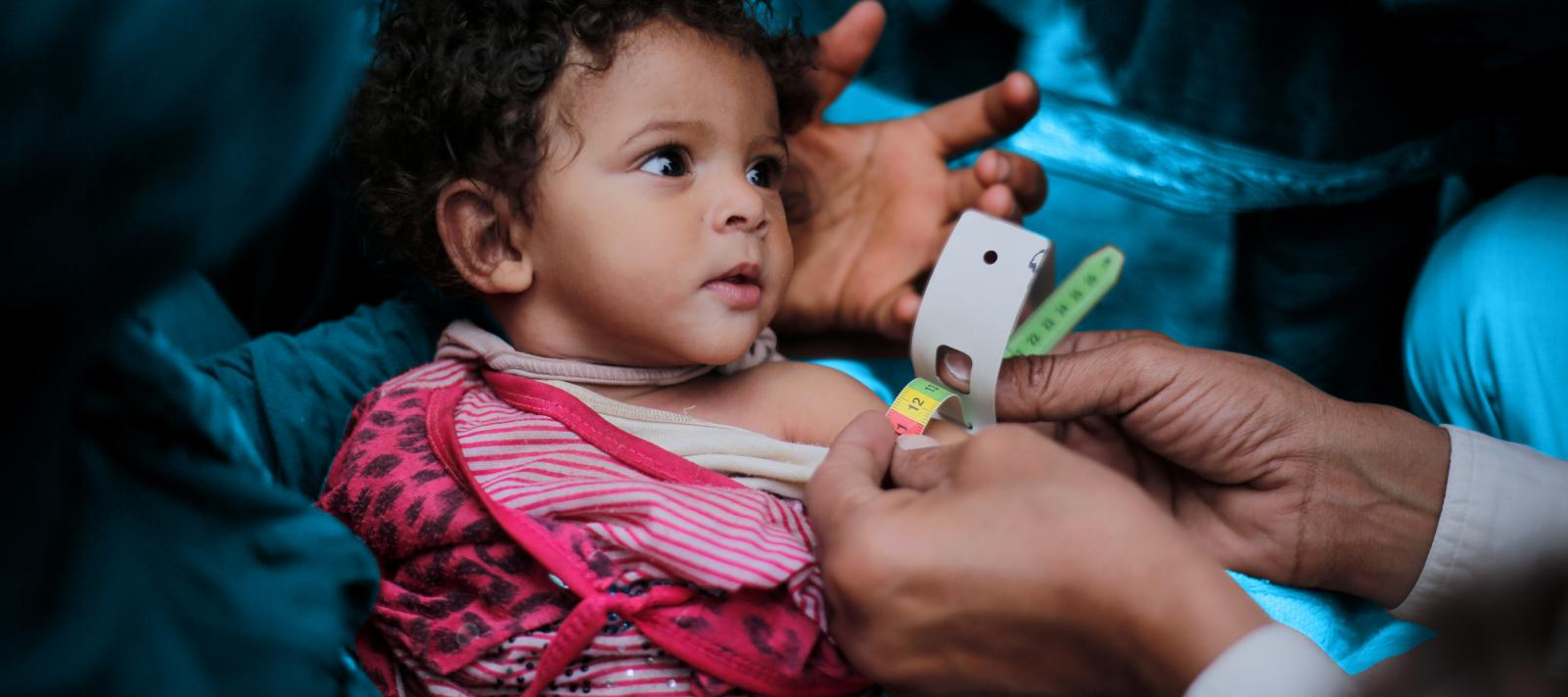 A child has her upper arm measured, Yemen