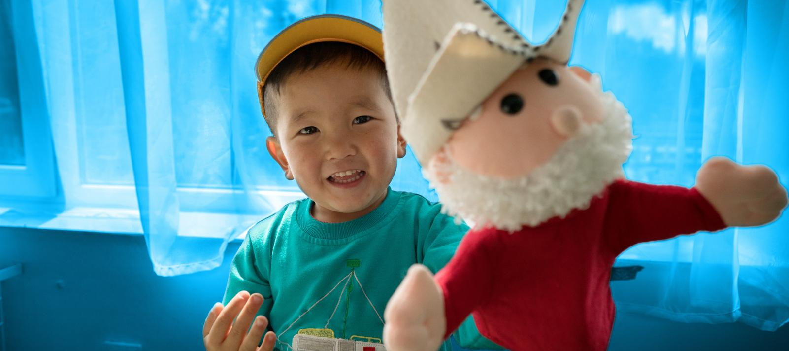 Smiling boy holds soft toy up to camera in Kyrgzstan.