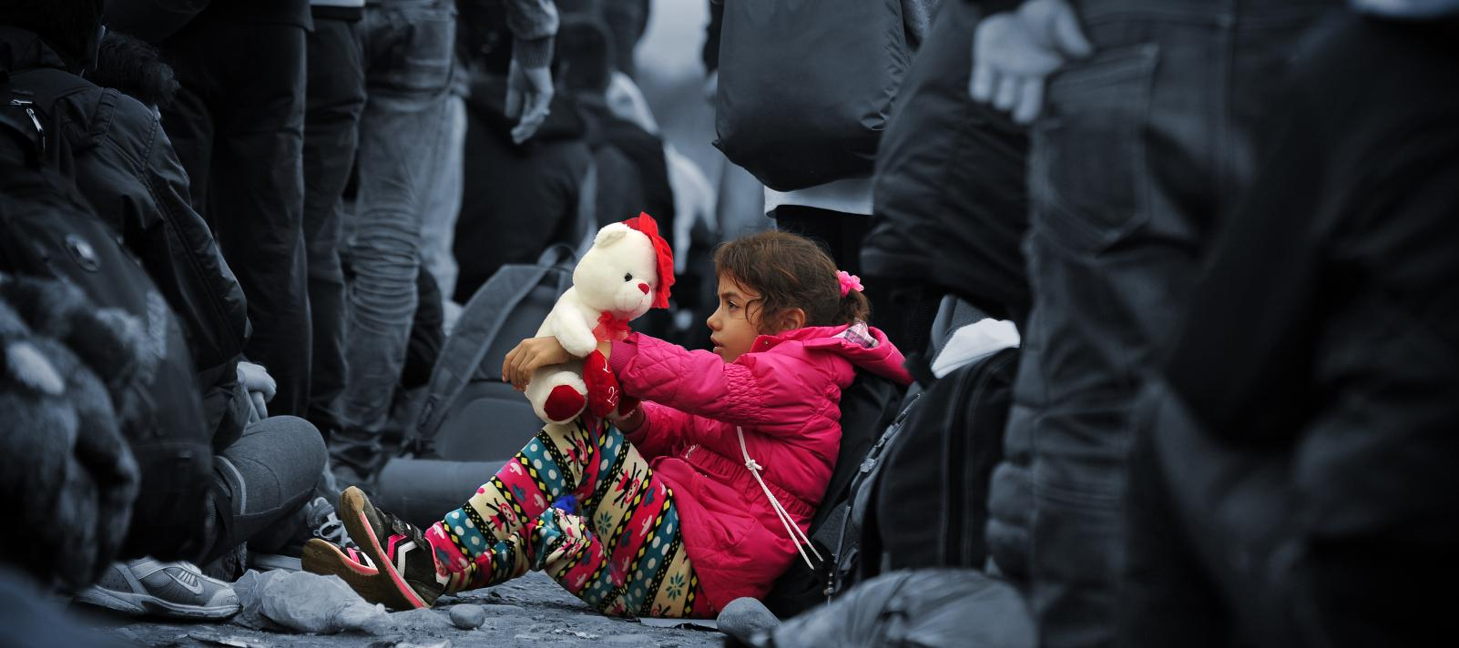 Girl sits on the ground holding her teddy bear
