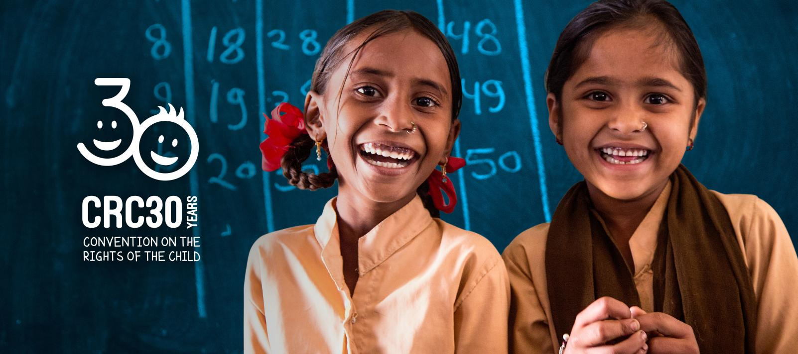 Convention on the Rights of the Child: A 7-year-old student and her best friend stand together in a school classroom in India.