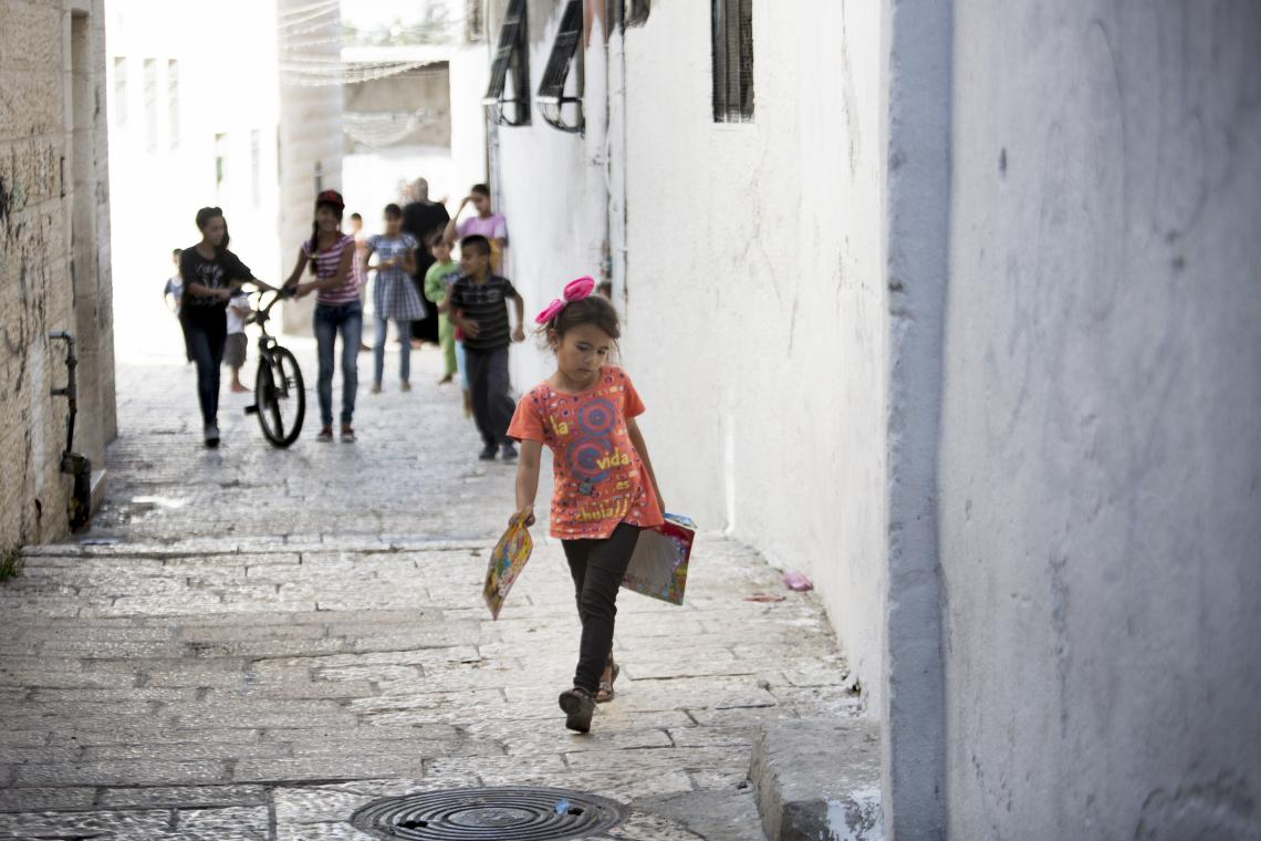 A girl carries books while walking through the Old City of Jerusalem.
