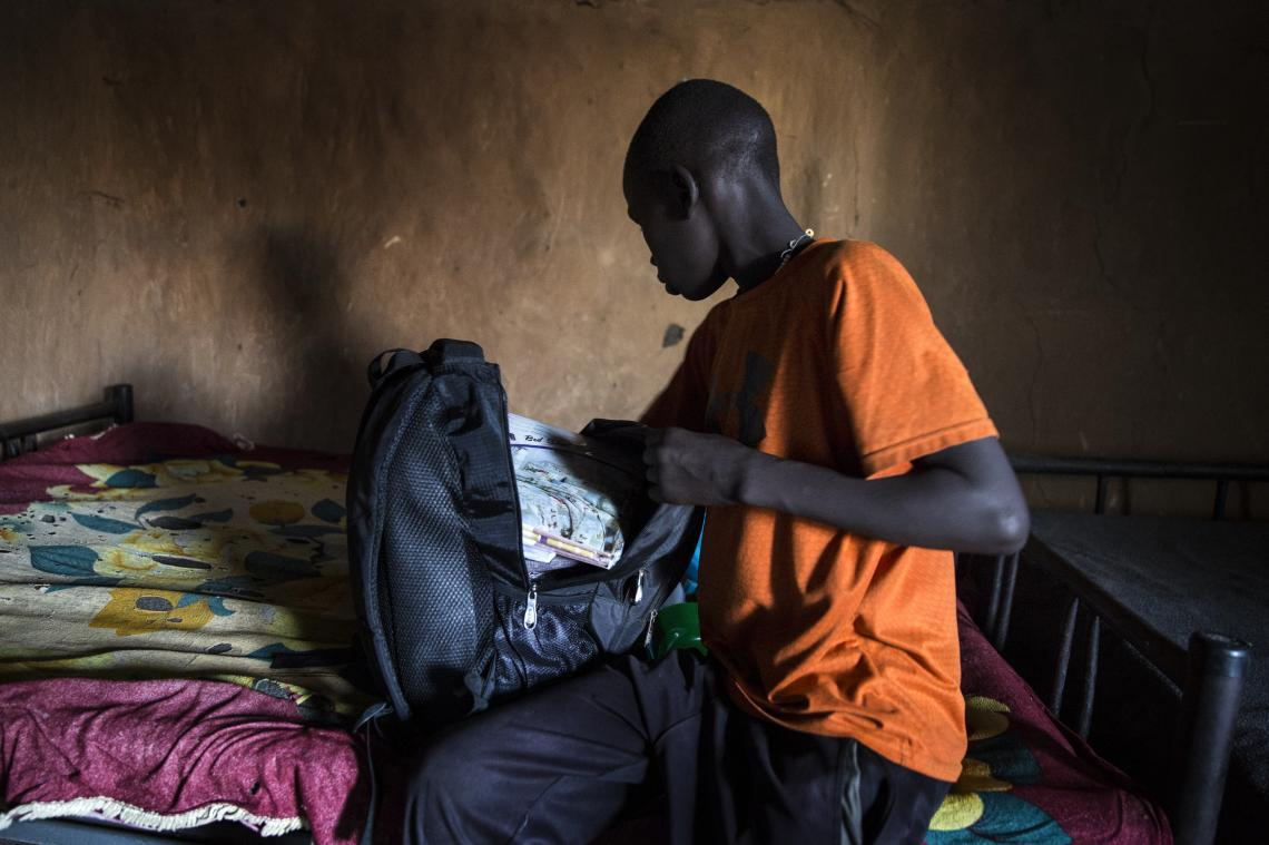 A boy packs his backpack, South Sudan