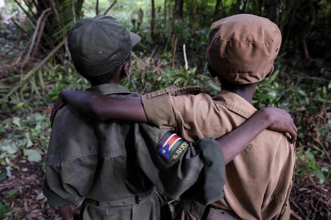 El 17 de abril de 2018 en Yambio, Sudán del Sur, [NOMBRES CAMBIADOS] (derecha-izquierda) Ganiko, de 12 años, y Jackson, de 13 años, se paran durante una ceremonia para liberar a los niños de las filas de los grupos armados y comenzar un proceso de reintegración.  Jackson y Ganiko eran mejores amigos cuando servían junto con el grupo armado.
