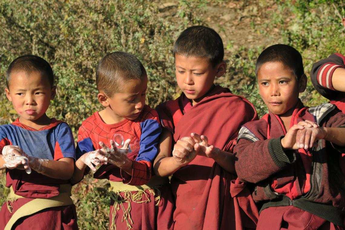 a group of monks are washing their hands with soap, Bhutan