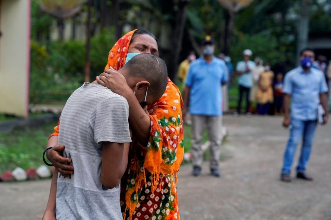 Bangladesh. A woman hugs a boy who is crying.