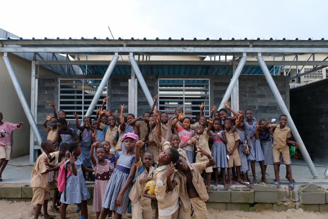 Children gather around the outside of a school, Côte d'Ivoire