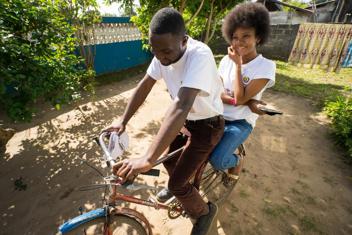 A teenage boy and girl ride on a bike, Mozambique.
