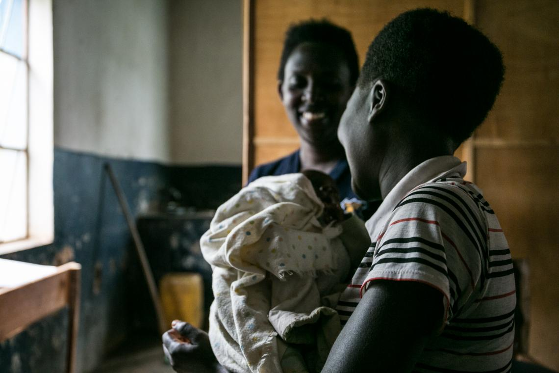 A woman smiles at another woman holding a baby, Burundi