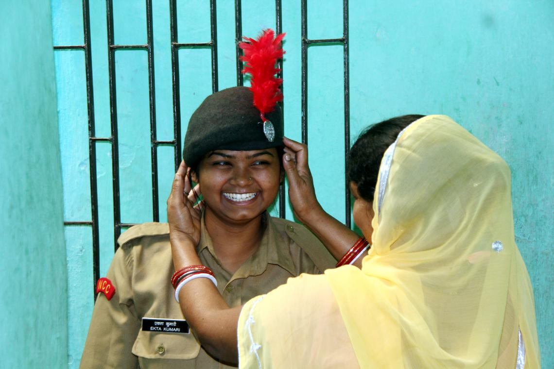 A girl proudly wears her National Cadet Corps uniform, while her mother lovingly adjusts her beret.