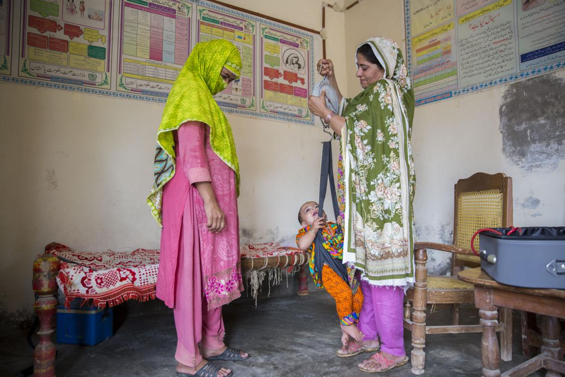 A health worker weighs a baby as the mother looks on, Pakistan