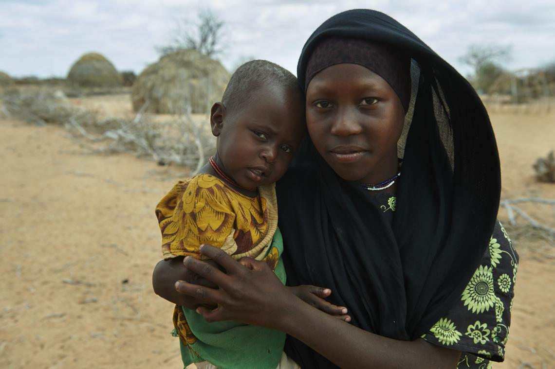 A girl holds her younger sister.