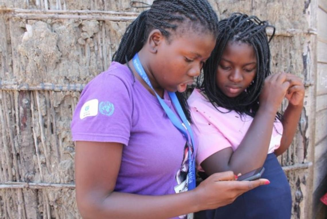 Two young women, one with a UNICEF badge, look at their phones