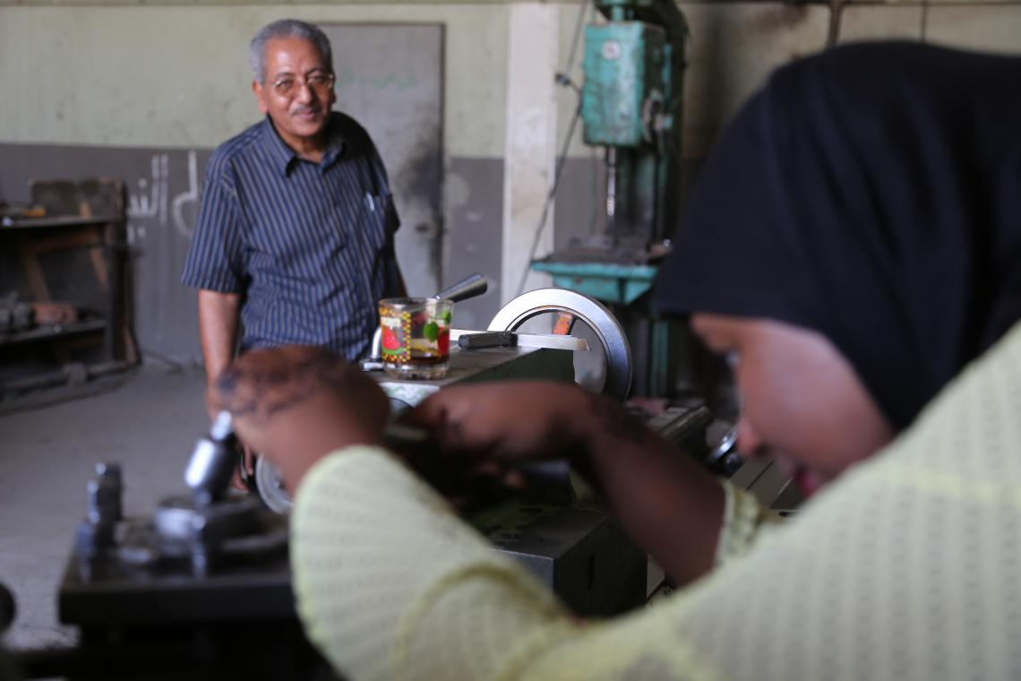 A father looks on as his daughter examines a piece of machinery, Egypt