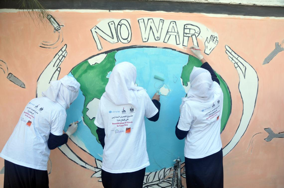 Children paint a mural on one of the schools in the Gaza Strip.