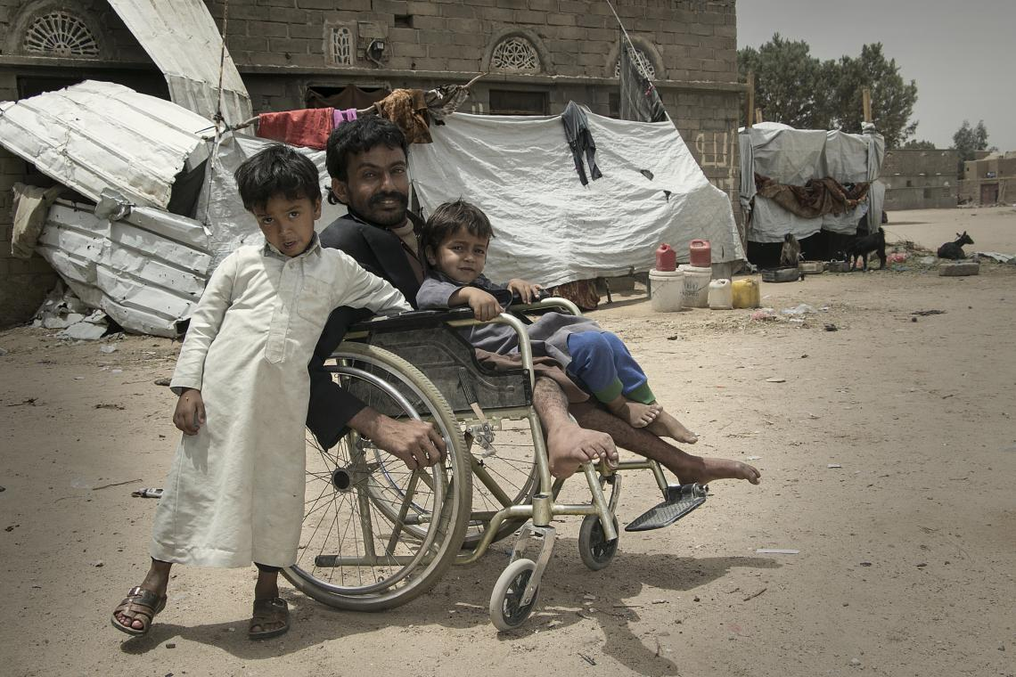 A man in a wheelchair with two sons, Yemen