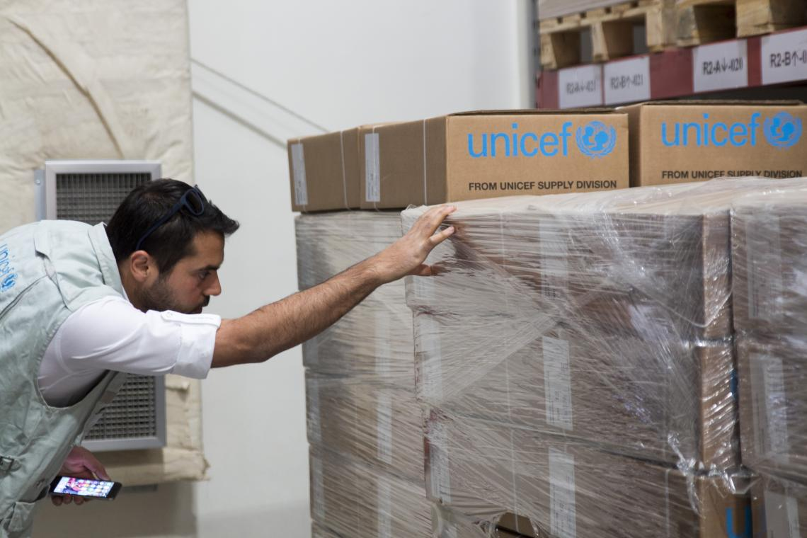A  logistics officer inspects boxes of health and nutrition supplies in a warehouse.