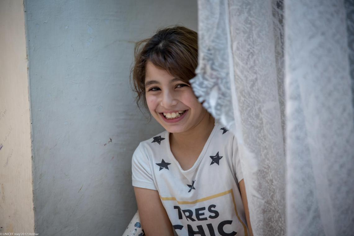 A 10-year-old girl smiles from behind a window in Iraq.