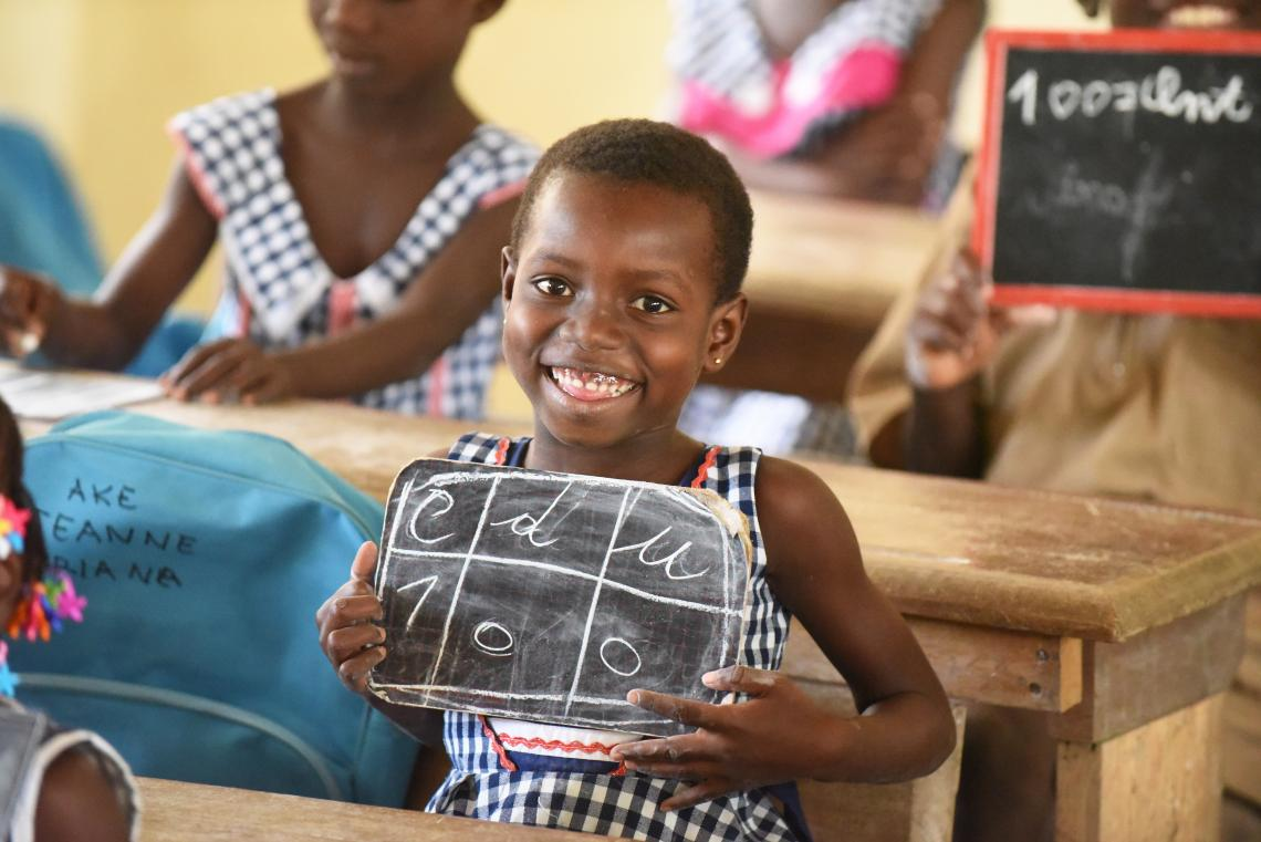 Una niña pequeña sonríe y sostiene una pizarra con su lección.