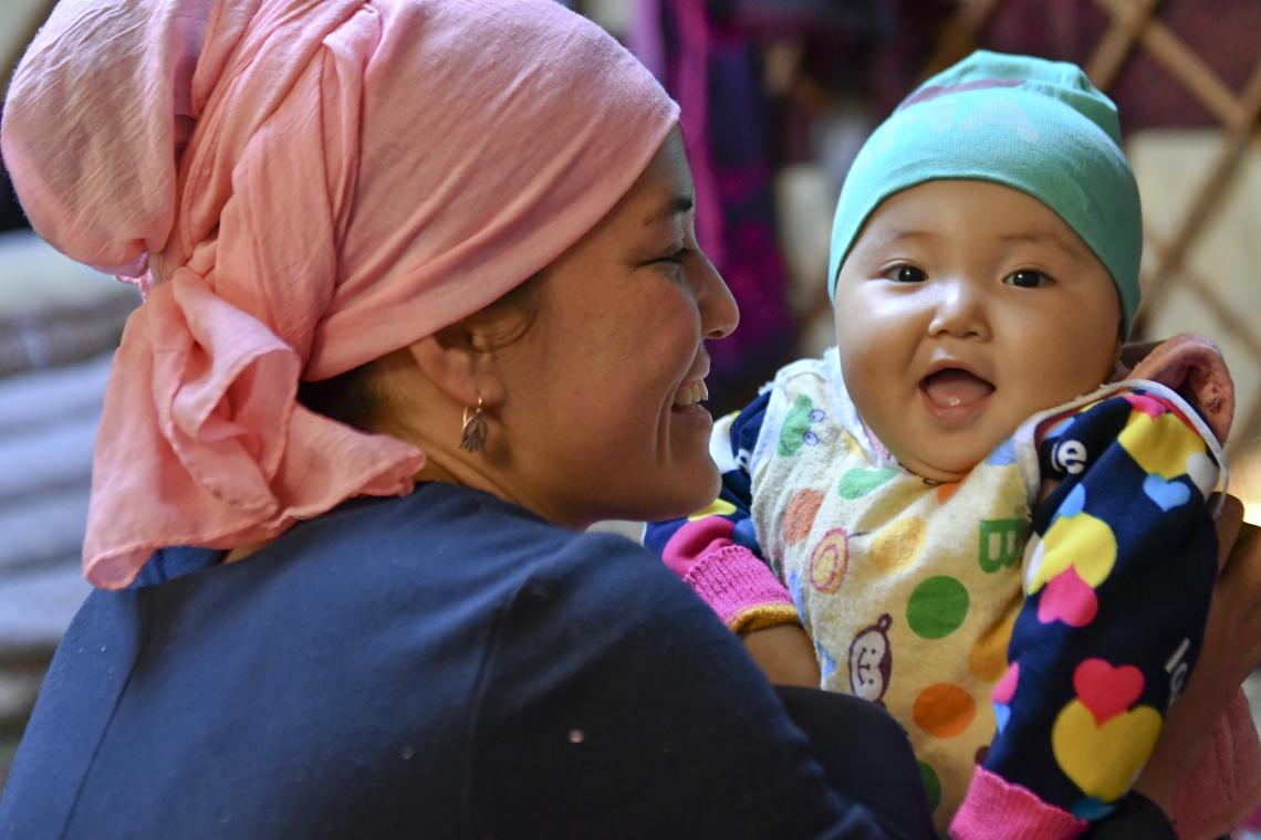 A girl smiles as she is held by her mother in Kyrgyzstan.