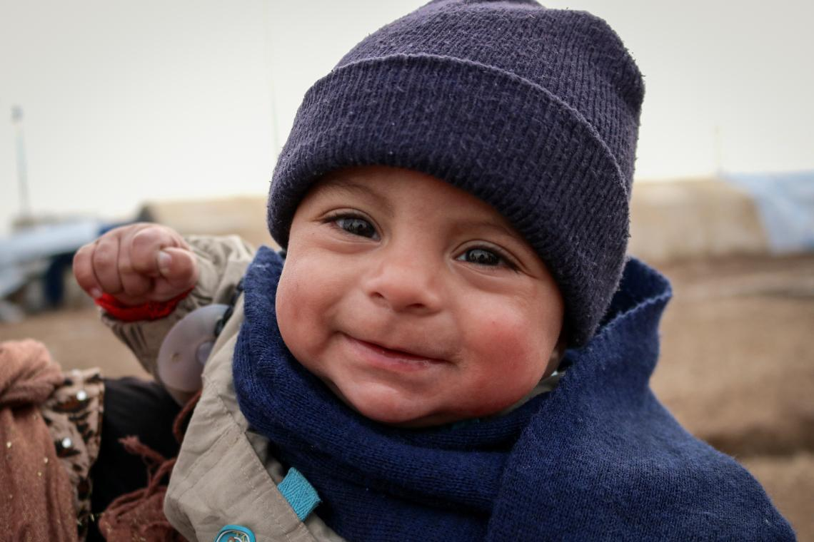 A boy in a winter hat smiles, Iraq