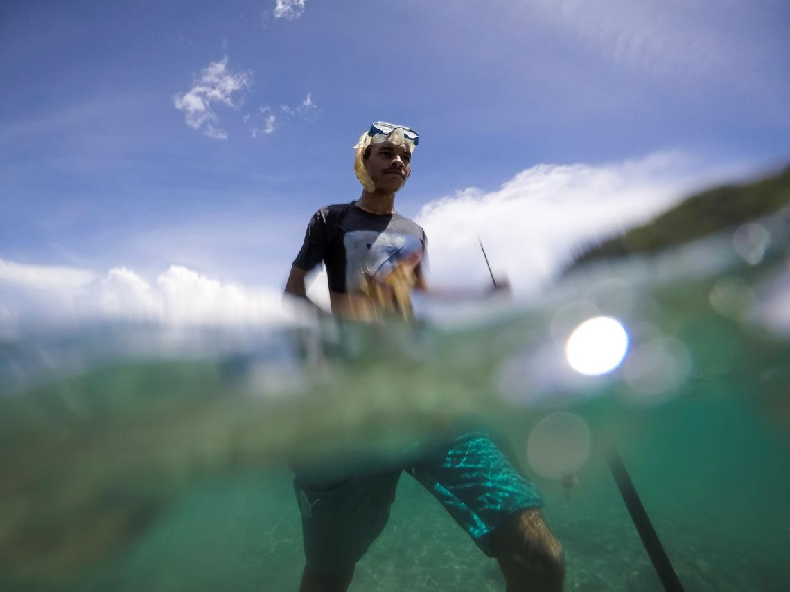 Timor-Leste. A teenage boy walks through water carrying a spear gun as he searches for fish in Timor-Leste.